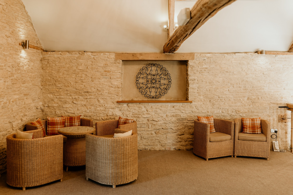 chairs and tables in the hallway at The Kingscote Barn Wedding venue by Cotswolds wedding photographers