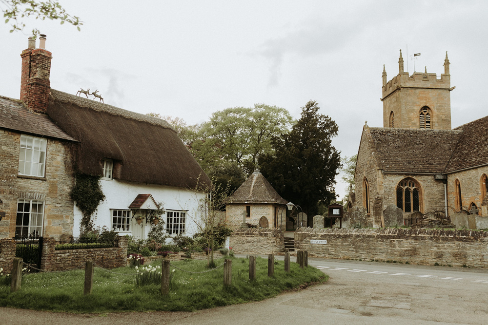 street and stone house and village church in the Cotswolds countryside