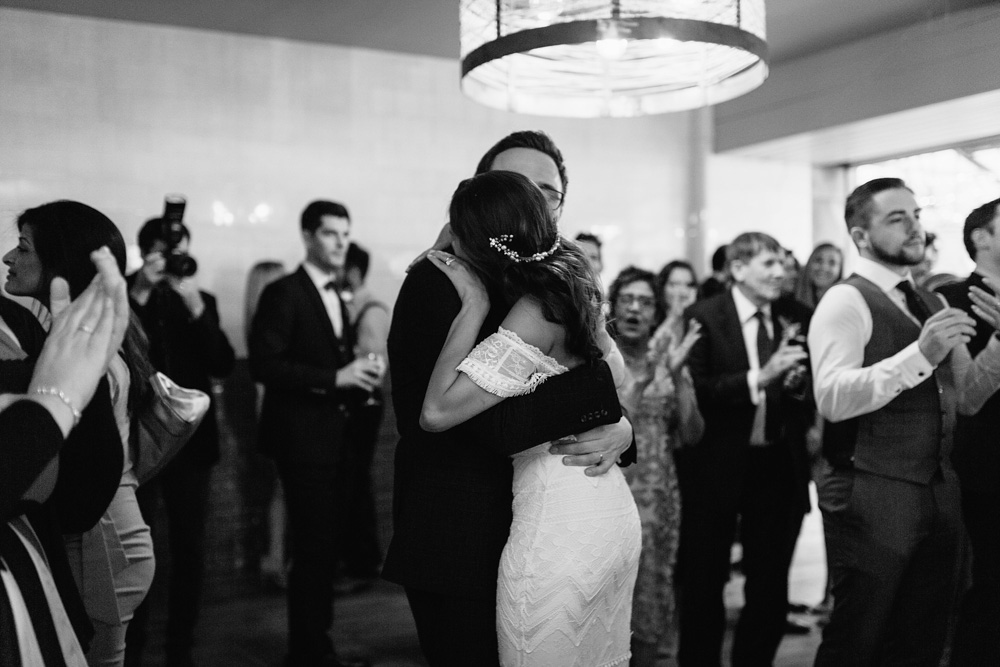 black and white image of bride and groom surrounded by guests on dance floor at plas dinam country house wedding reception