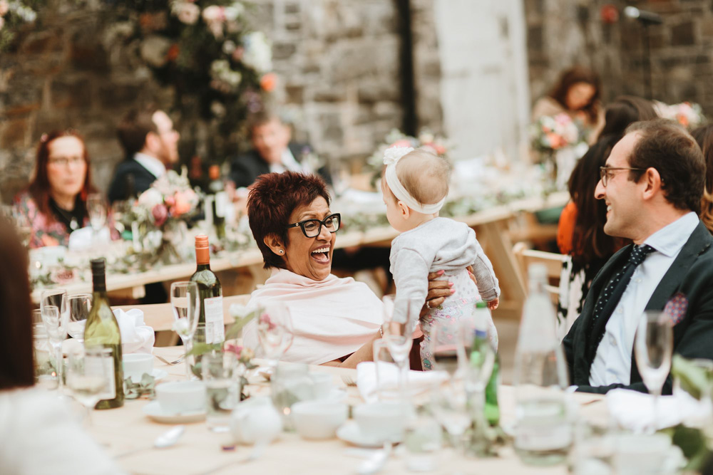 mom laughing with baby at plas dinam country house wedding reception Wales