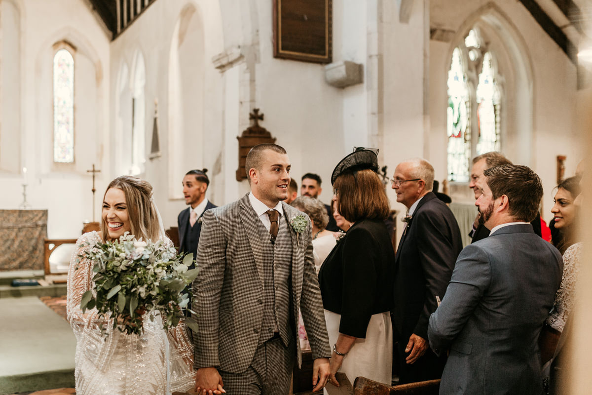 bride and groom walking down the aisle during the church wedding ceremony by Canterbury wedding photographers