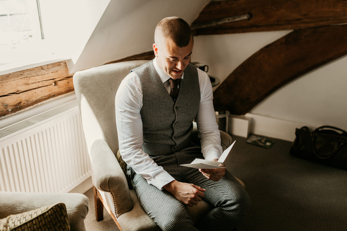 groom wearing an asos suit reading a letter from the bride in the morning