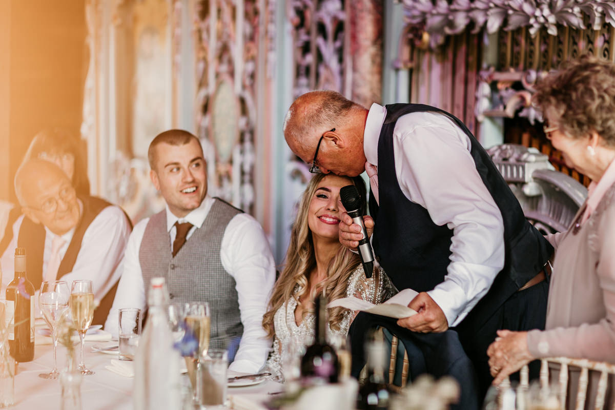 father kissing bride on forehead during the wedding speeches at preston court wedding venue by Canterbury wedding photographers