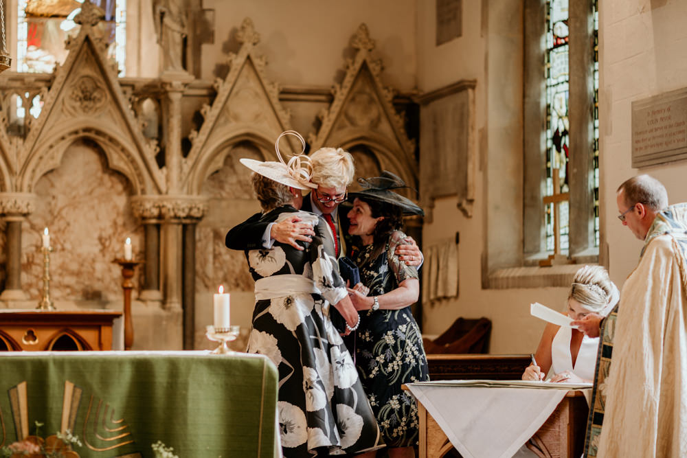 groom hugging moms during church wedding ceremony Chichester