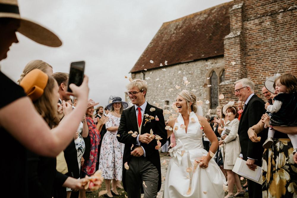 bride and groom walking through confetti after church wedding ceremony