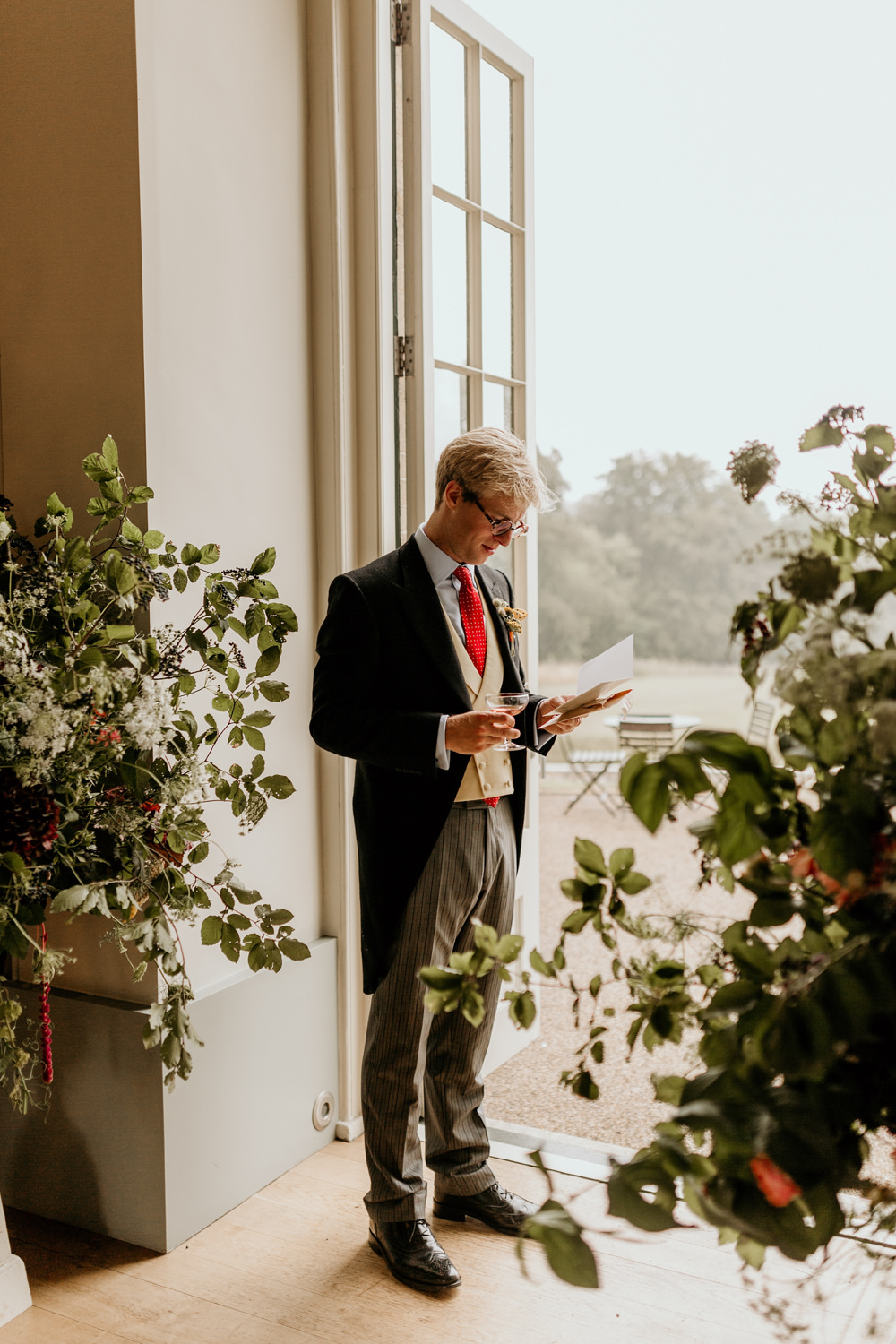 groom reading a love letter from his bride by the door at The Kennels Goodwood wedding venue England