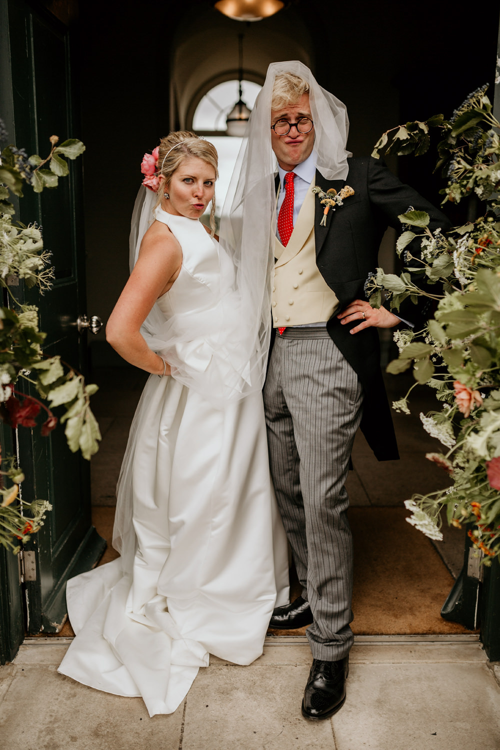 funny bride and groom portraits at The Kennels Goodwood wedding venue by wedding photographer