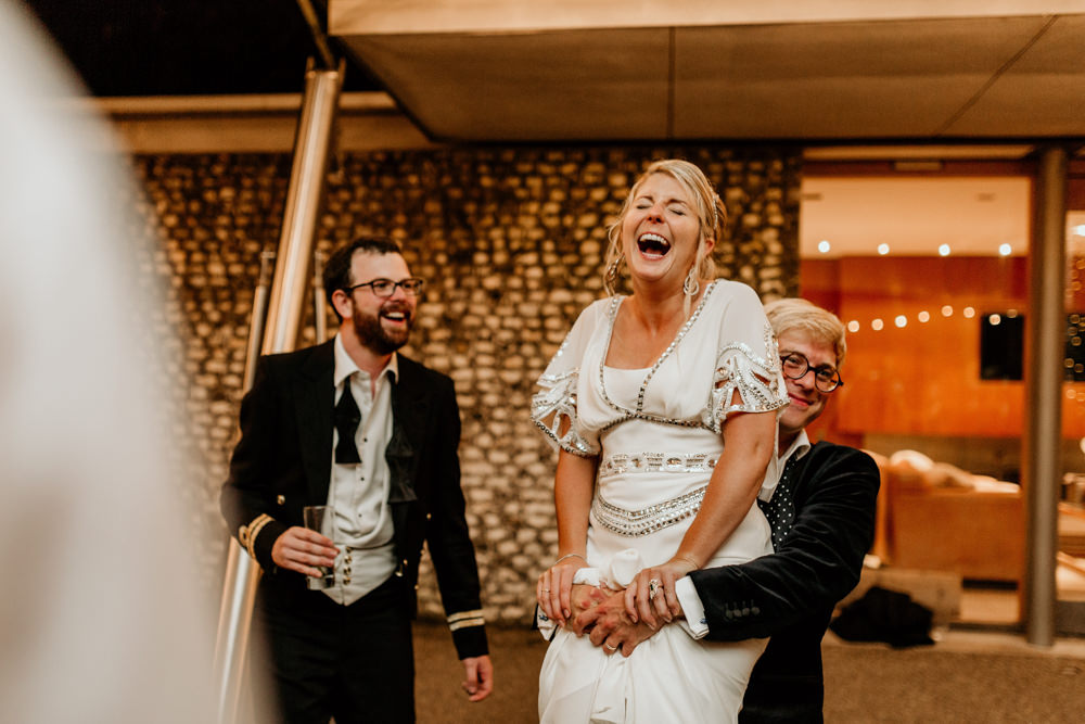 groom lifting bride wearing an Alice Temperley wedding dress at The Kennels Goodwood wedding reception