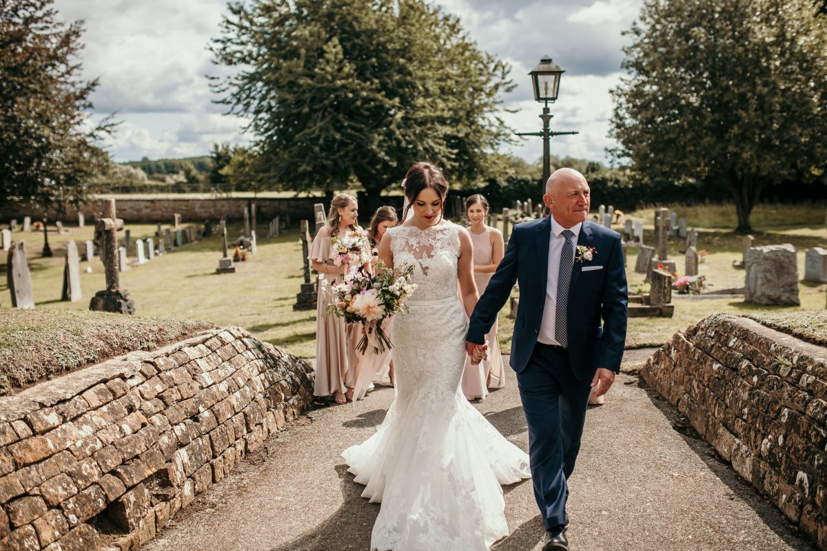 bride and father walking to church with bridesmaids in the back by Cotswolds wedding photographer