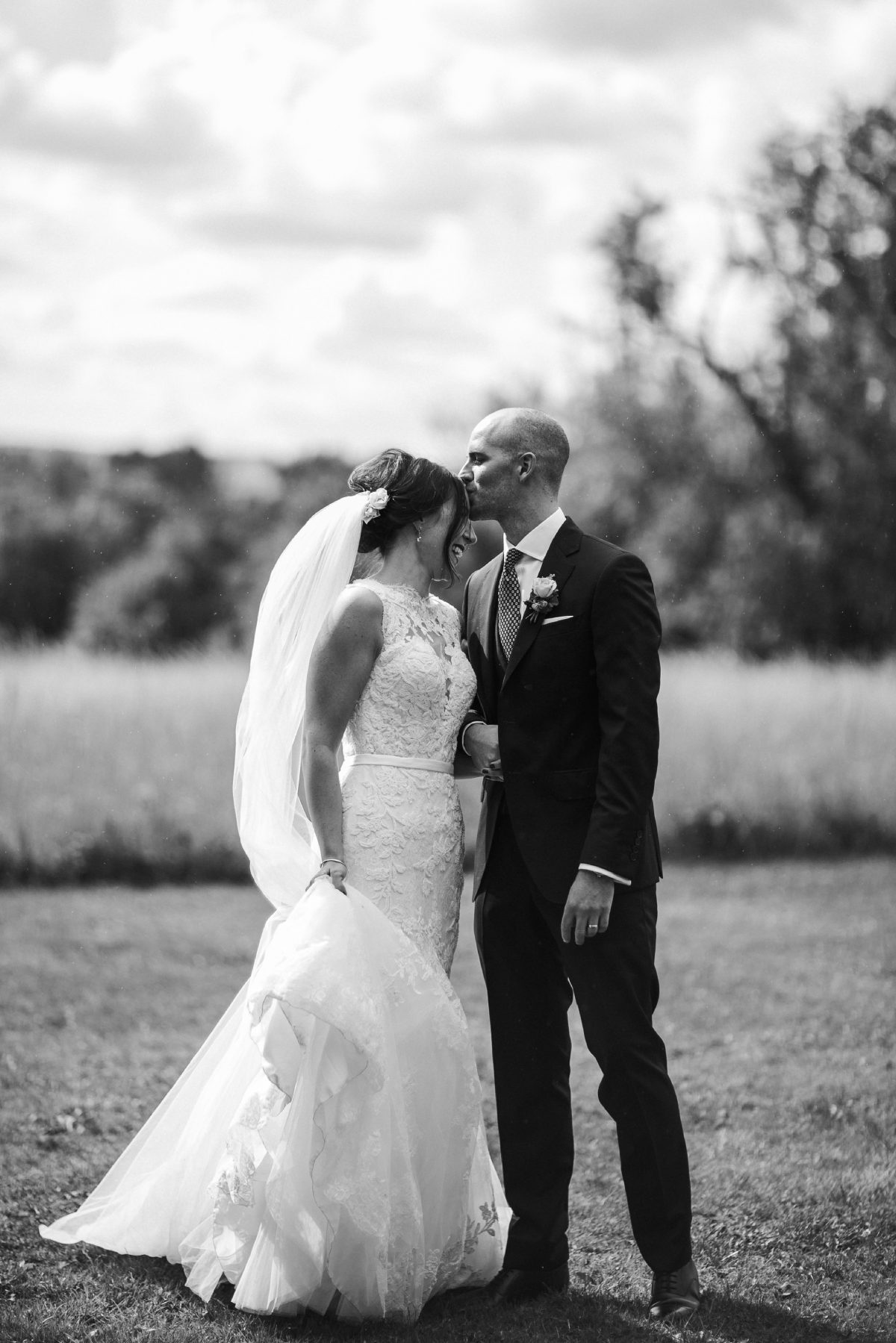 black and white image of bride and groom kiss during the wedding portrait at Merriscourt Barn Wedding venue by Cotswolds wedding photographer