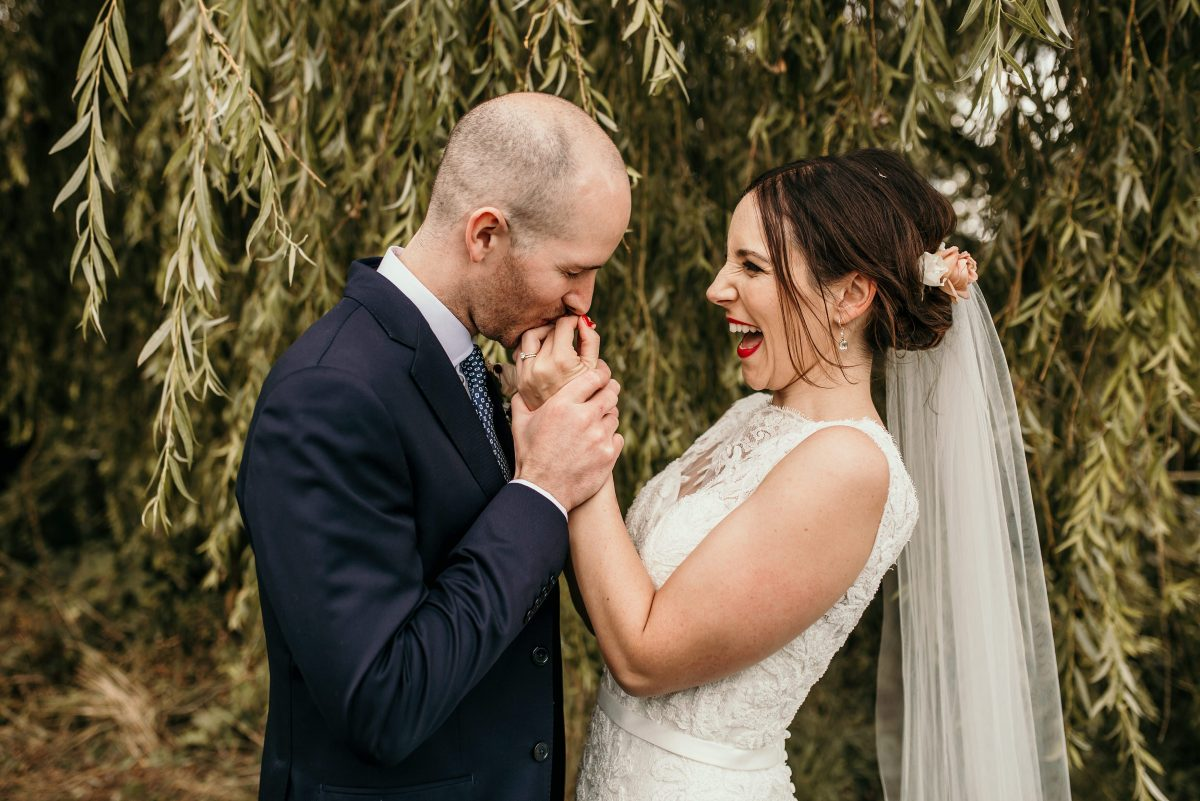 groom kissing brides hand at Merriscourt Barn Wedding venue by Cotswolds wedding photographer