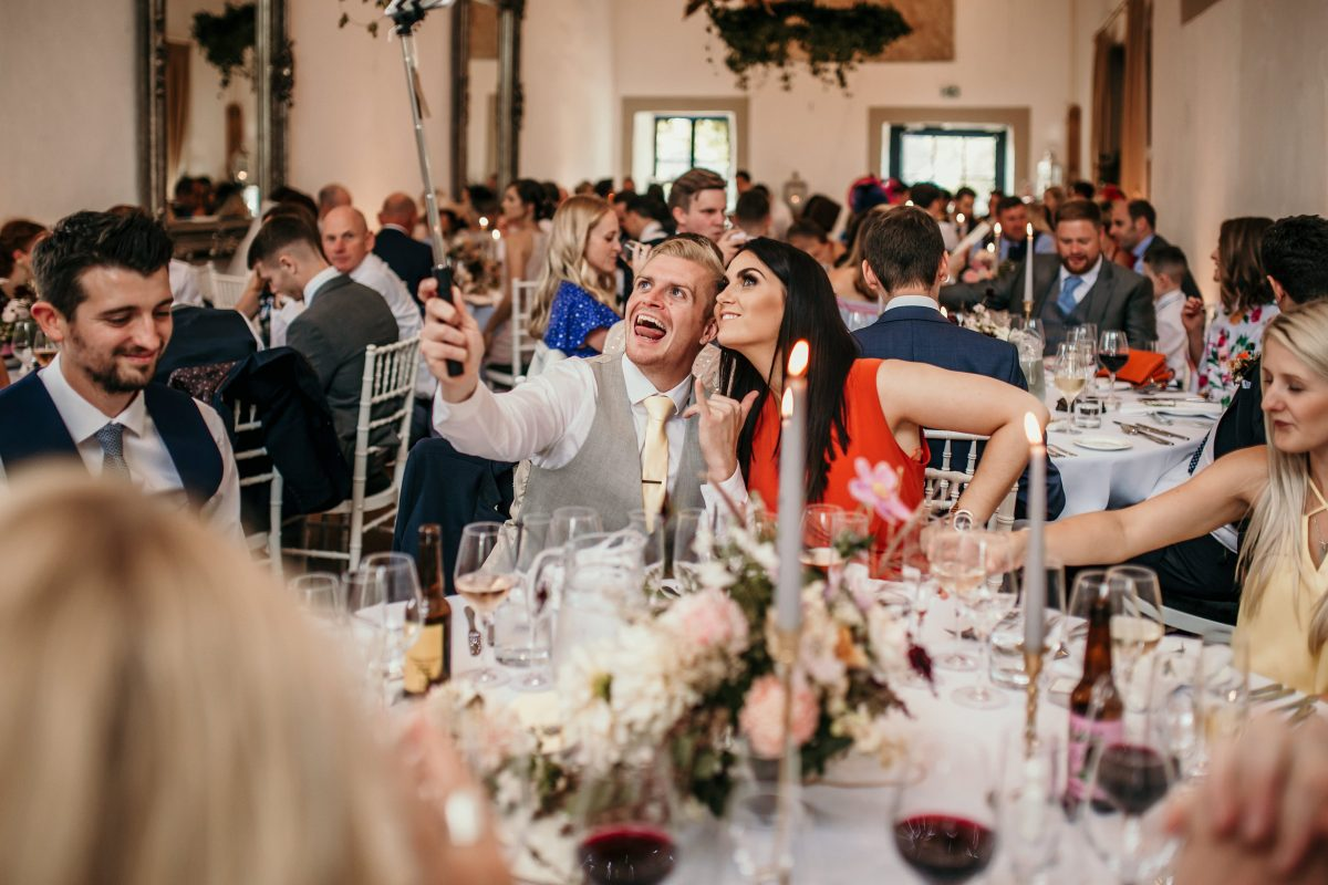 guests taking selfies at table during the wedding reception at Merriscourt Barn Wedding venue by Cotswolds wedding photographer