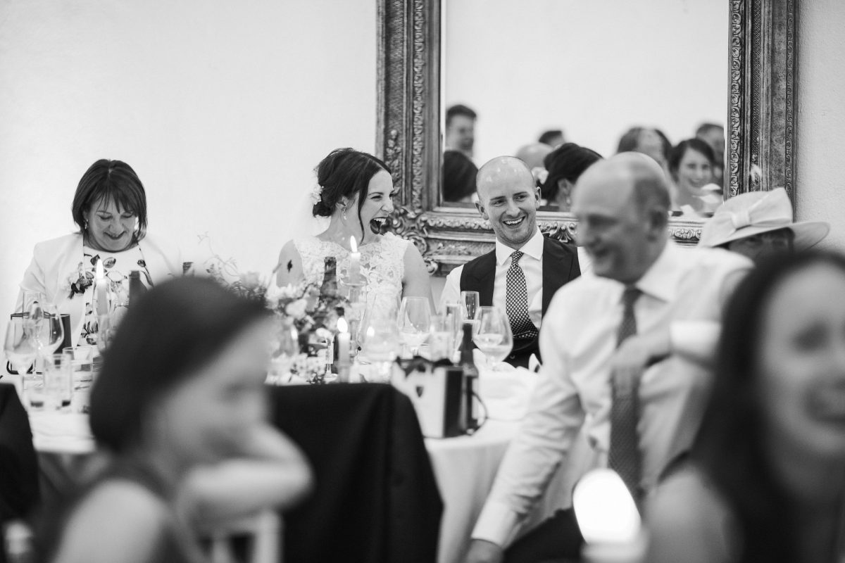 black and white image of bride and groom smiling during wedding speeches at Merriscourt Barn Wedding venue by Cotswolds wedding photographer