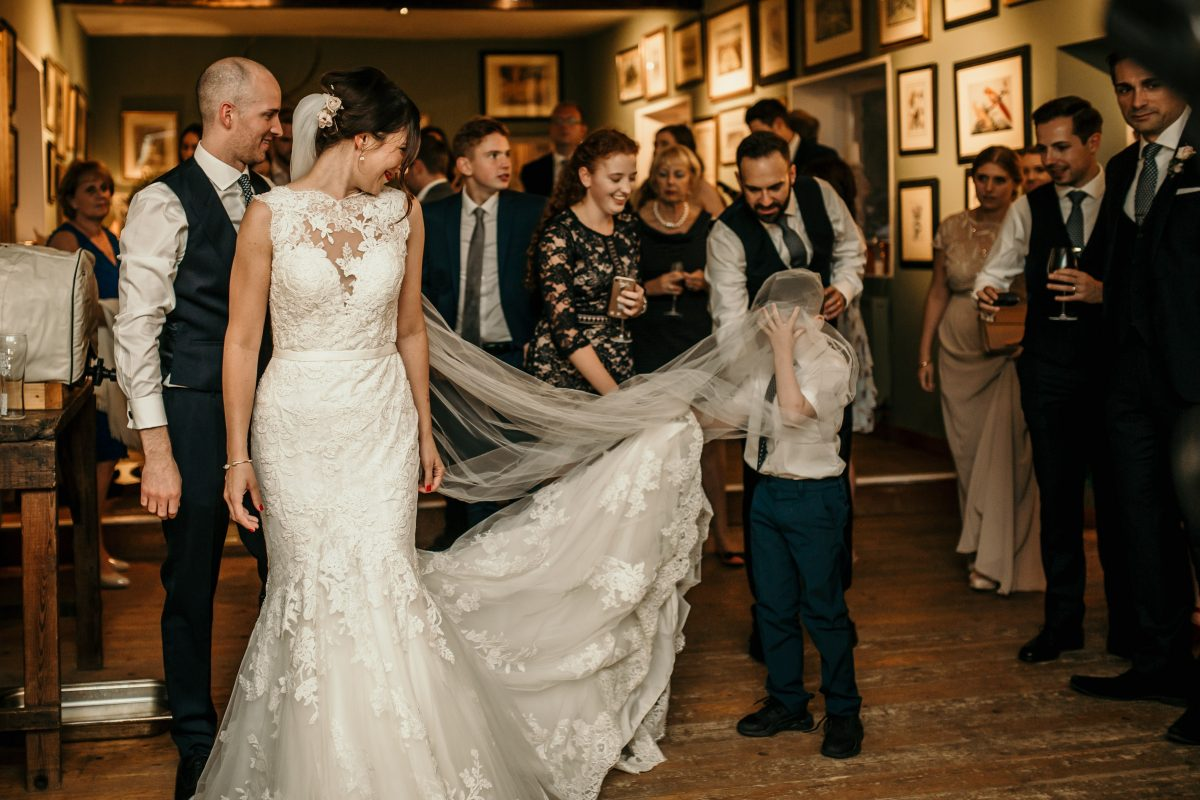 little boy under the wedding veil during the reception at Merriscourt Barn Wedding venue by Cotswolds wedding photographer