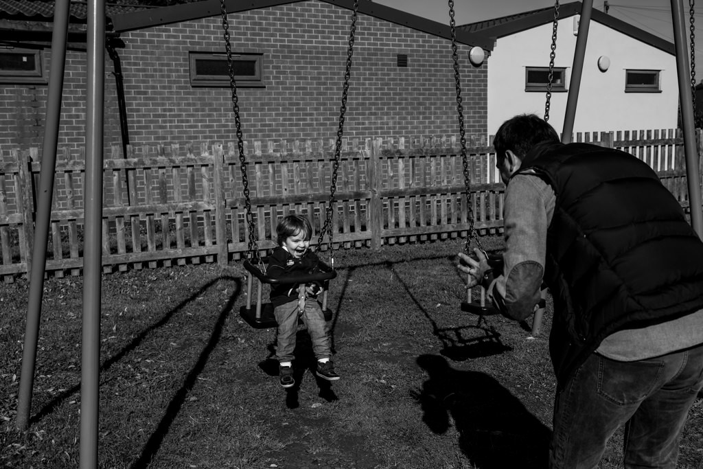 daddy playing pushing boy on the swing in the park