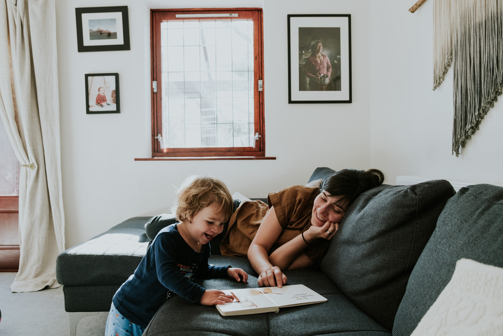 mommy reading a book with the baby boy in the living room
