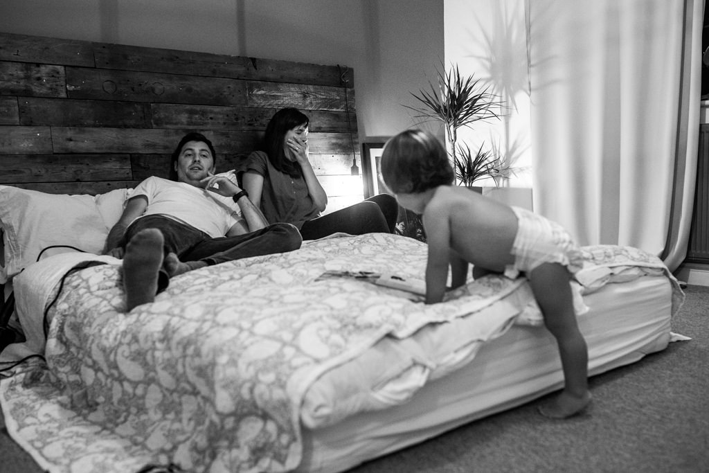 parents tired in the evening and baby boy in nappy climbing on the bed