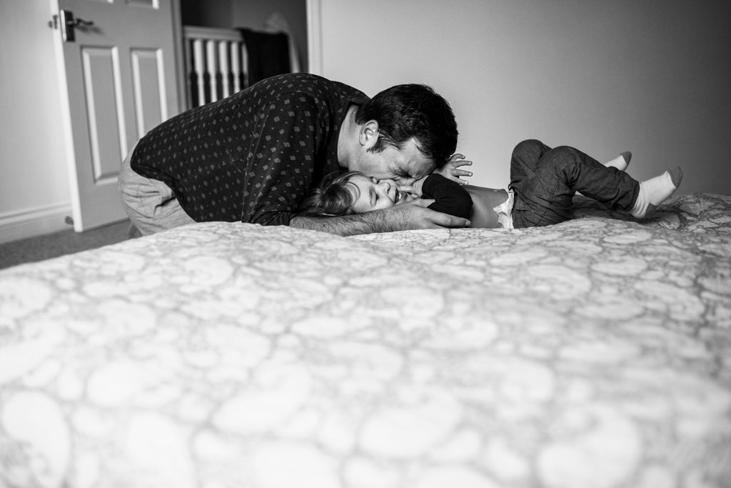 daddy and boy playing on the bed in the morning