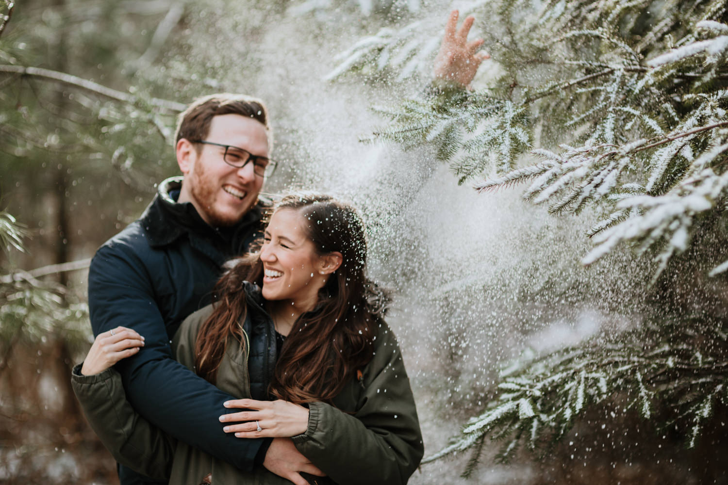 couple playing with snow during the engagement shoot at Wyre forest in England