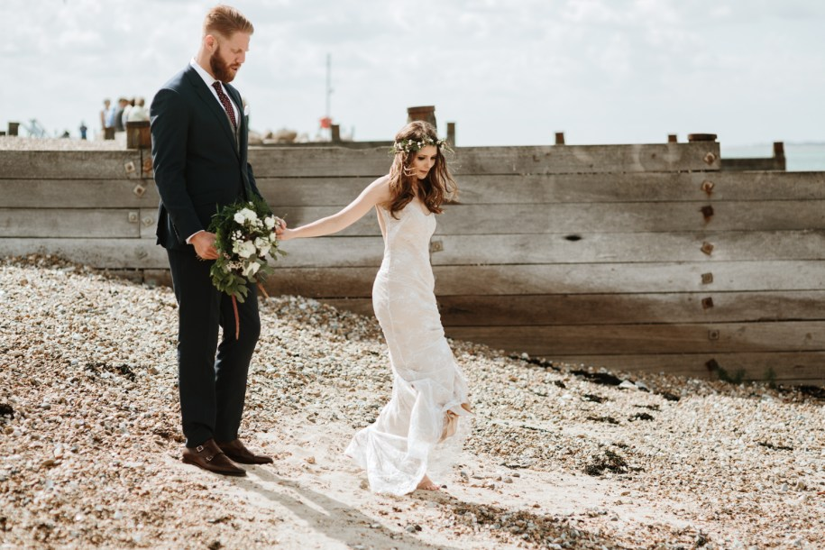 bride and groom walking down a beach with a bohemian wedding bouquet