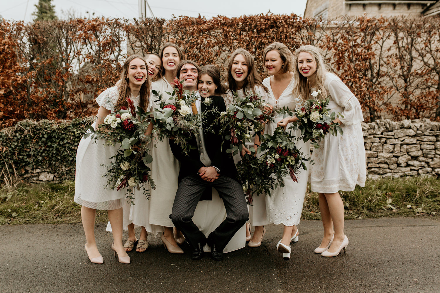 bride and bridesmaids dressed in white , posing for a fun group photo