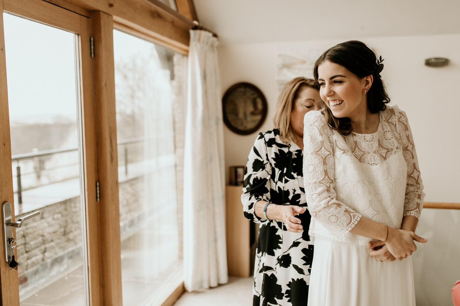 bride getting ready in the morning with mom helping put on her dress, for her Stroud wedding Cotswolds
