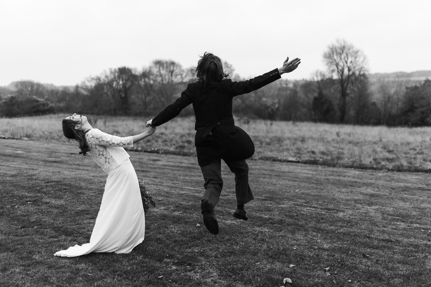 black and white image of fun couple during their wedding portraits at Stroud by Cotswolds wedding photographers
