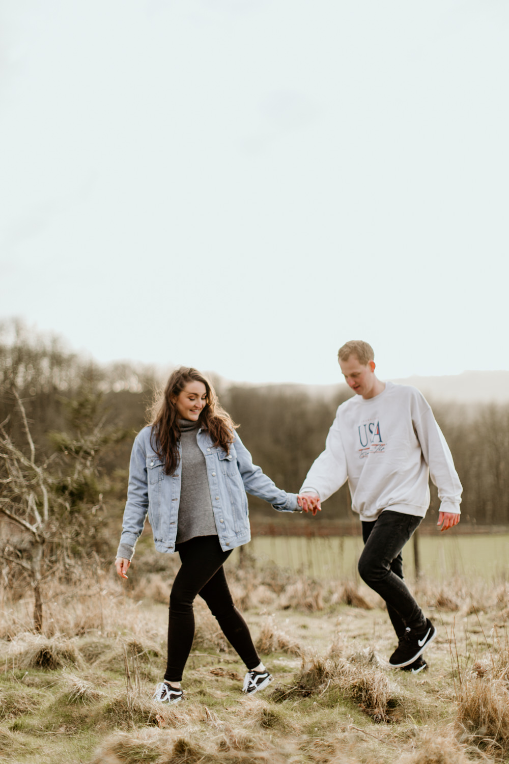 engaged couple walking hand in hand on a field near Broadway Tower in the Cotswolds during their engagement session