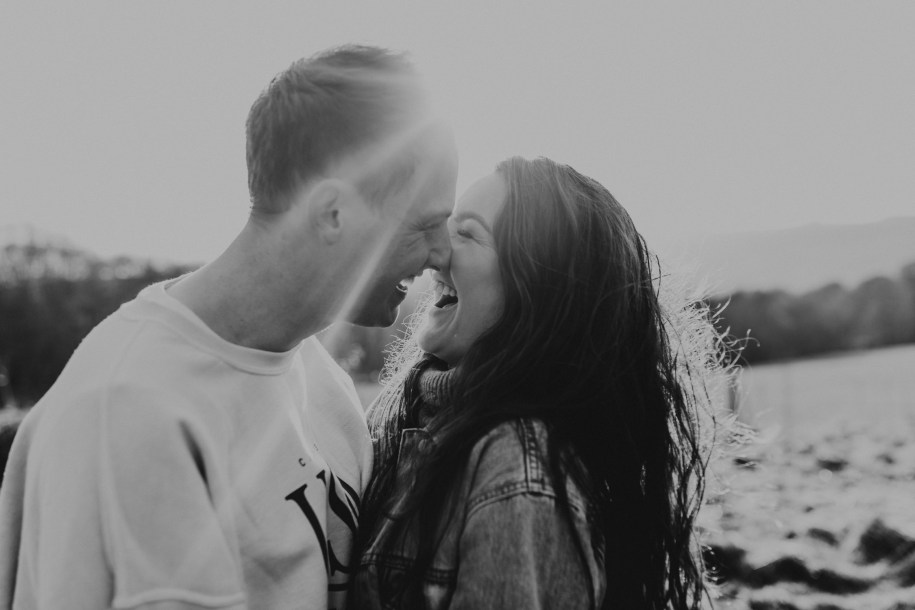 black and white image of couple kissing and laughing during their engagement session in the Cotswolds countryside