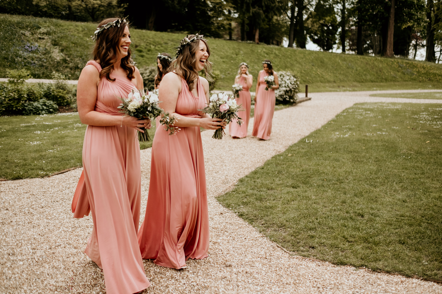 bridesmaids walking down towards the wedding cermeony in their coral multi way wear bridesmaids dresses