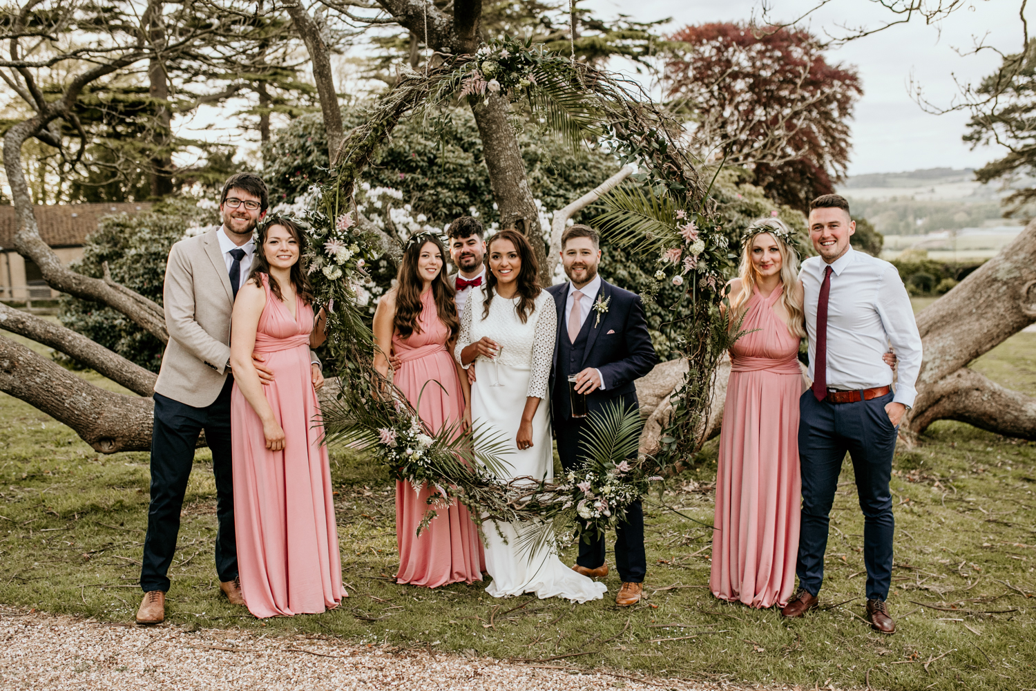 group photo with bridesmaids in front of foliage circle at Coombe Lodge Blagdon wedding venue