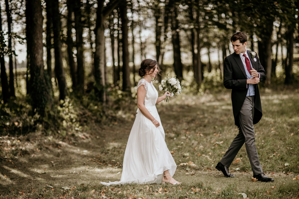 bride and groom walking during a portrait session in Poulton