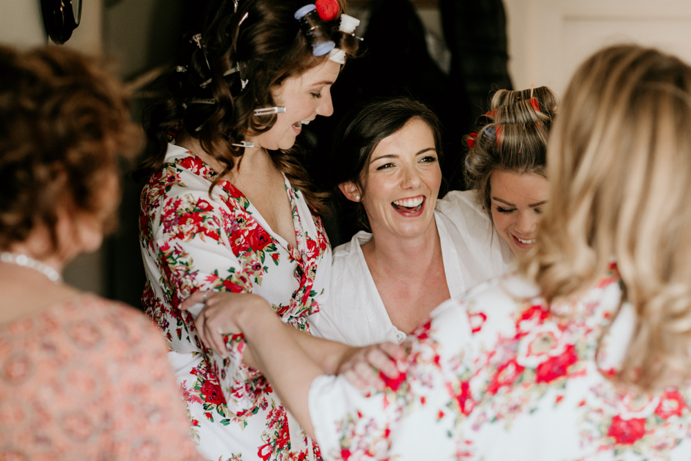 bride and bridesmaids hug during the morning prep in Poulton