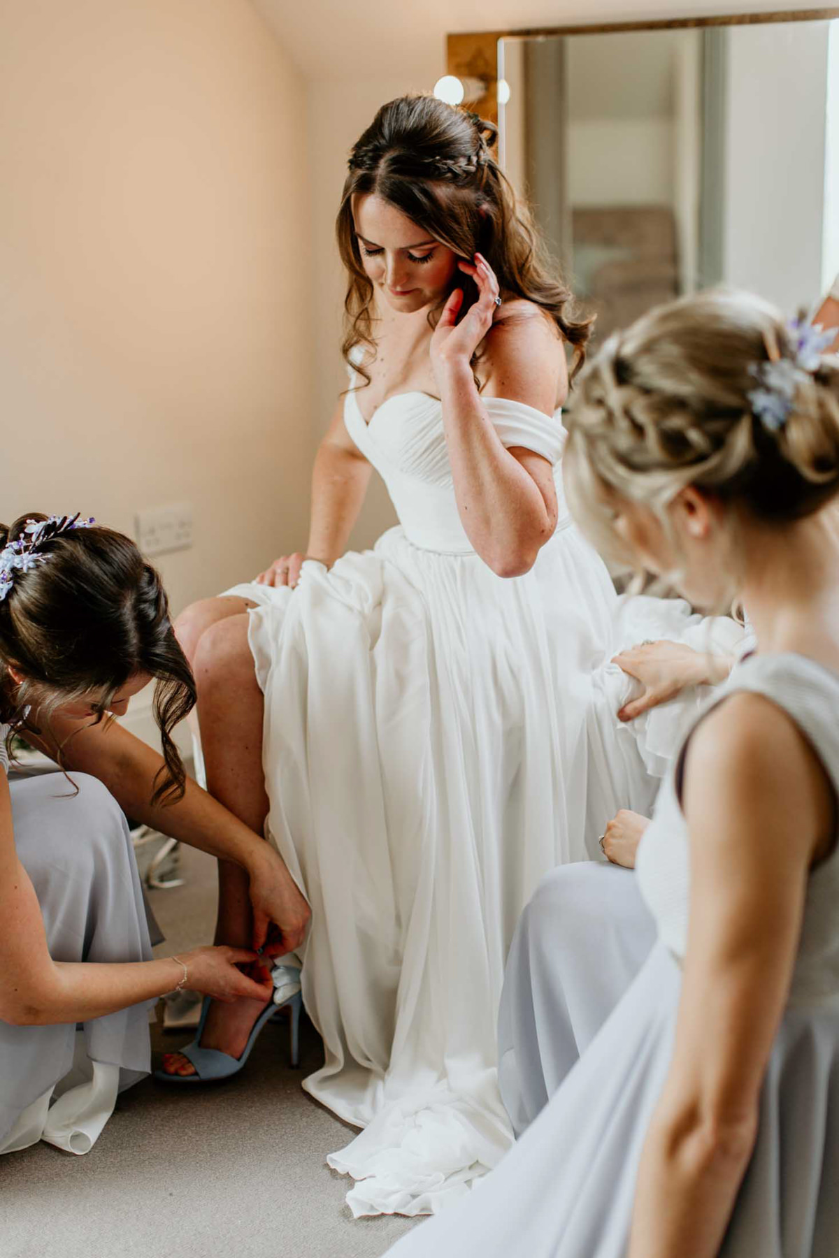 bridesmaids helping bride getting wedding shoes on before her wedding ceremony