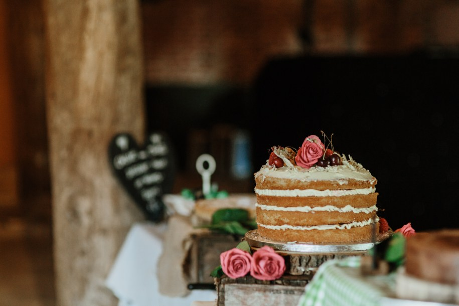 simple naked cake with roses and cream for a barn wedding