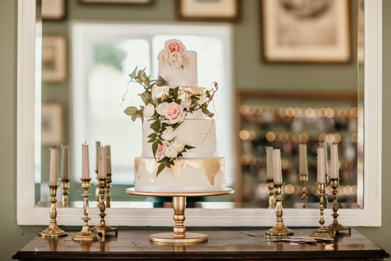 white wedding cake with roses and golden leaf