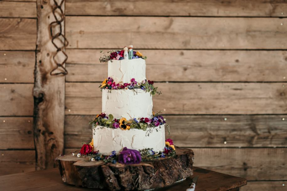 homemade wedding cake with edible flowers on a wooden log