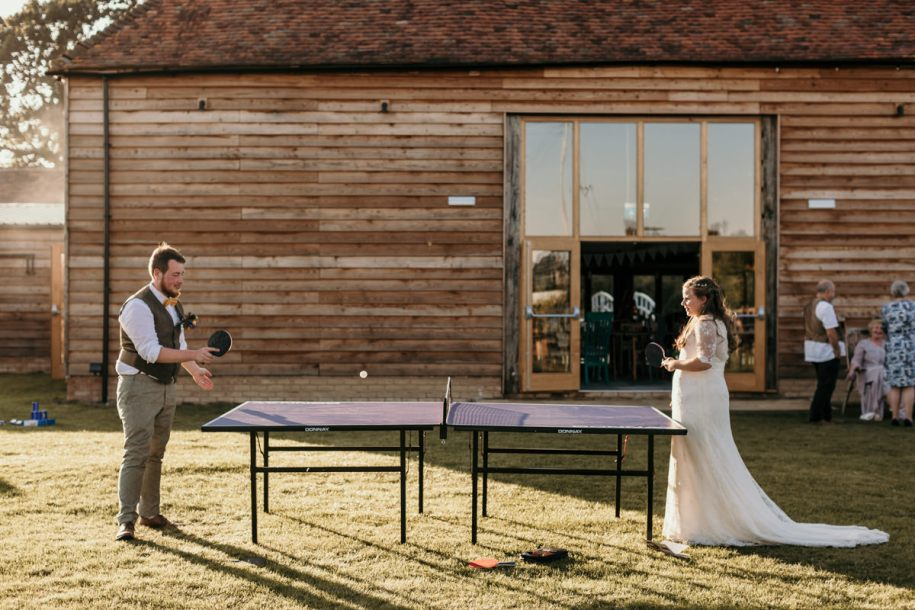 bride and groom playing ping pong during the wedding cocktail hour games