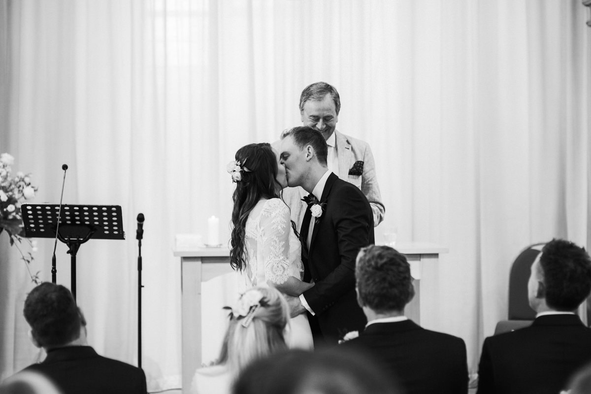 black and white image of first kiss between bride and groom at church during the wedding ceremony