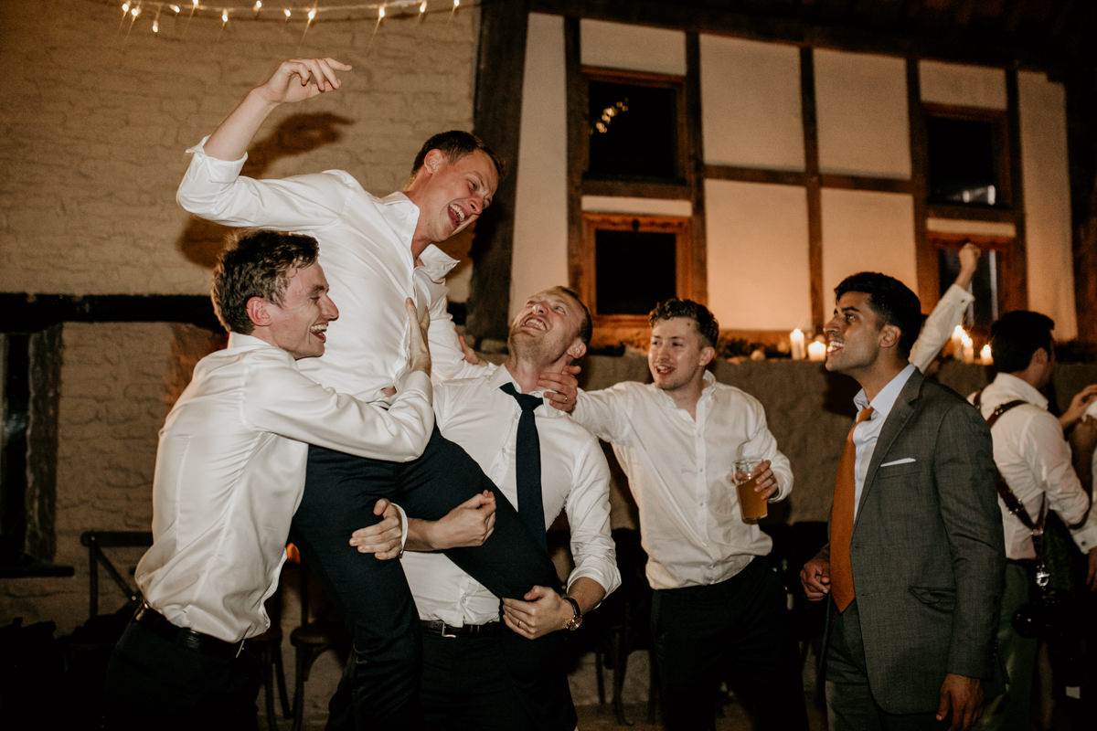 groom lifted on shoulders during the wedding reception at Priors Court Barn