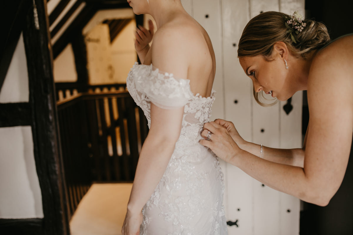 bride getting dressed in her Essence wedding dress for her Shustoke Barn wedding