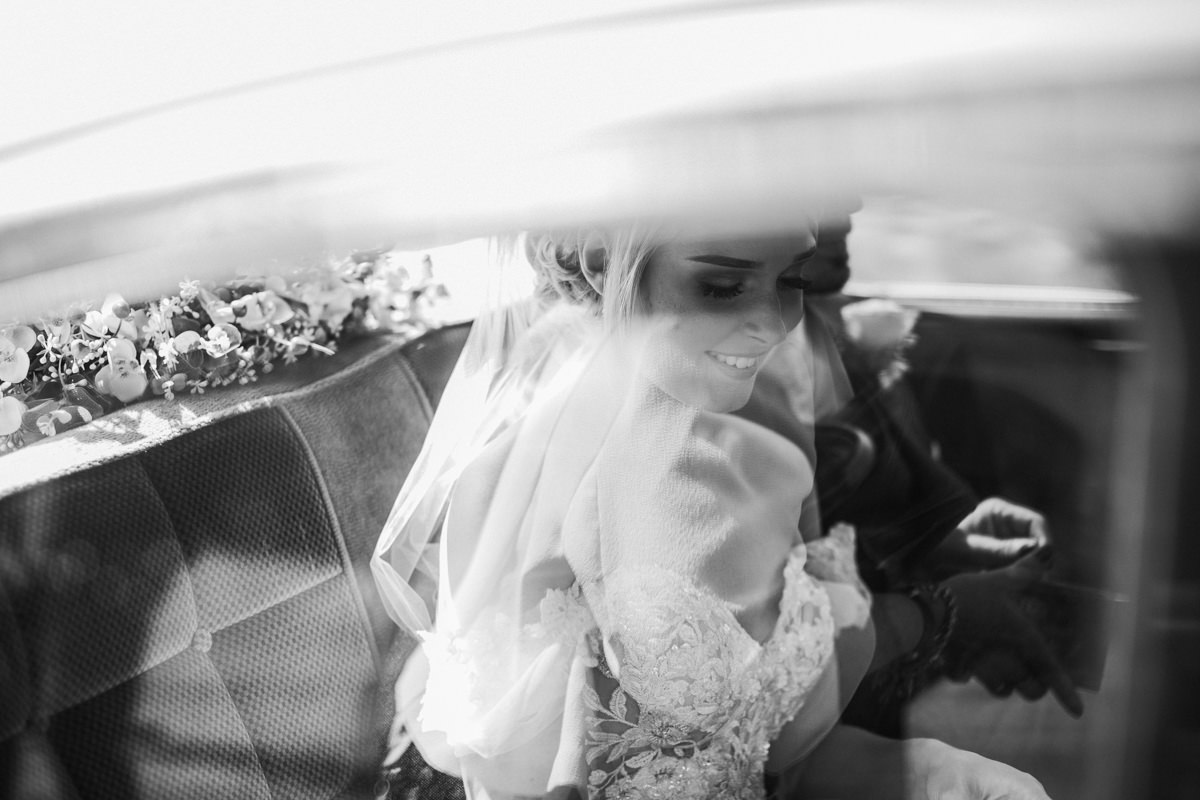 black and white picture of bride and groom through the car's window after the wedding ceremony