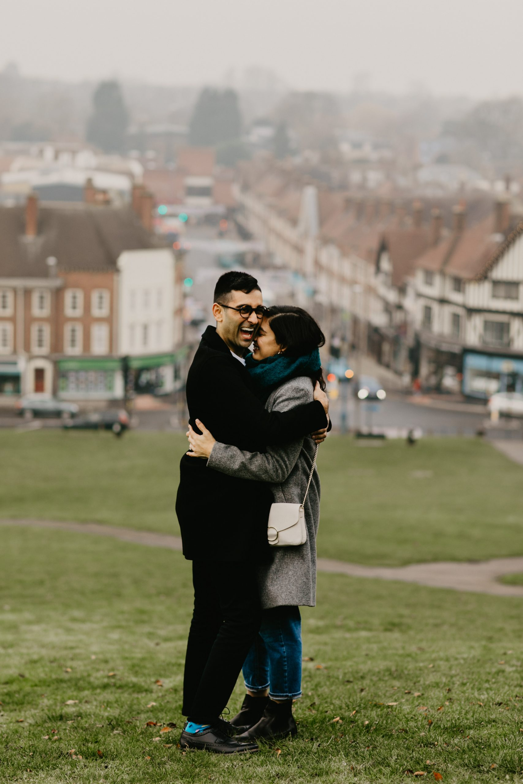 couple hugging and smiling after their proposal on a hill near london in 2020