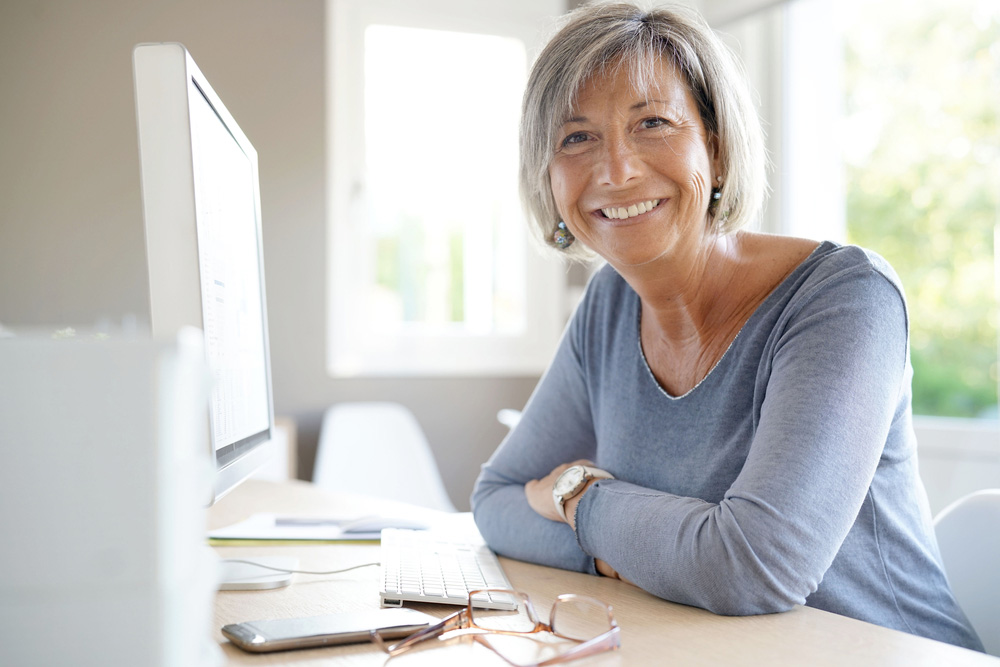 Older woman sitting at her computer and smiling confidently