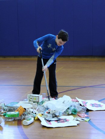 """A student sorting items from """"Trash Mountain."""""""