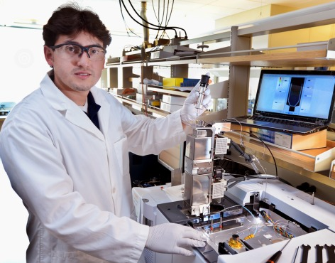 Juan Proano Aviles, an Iowa State doctoral student in mechanical engineering, uses a micropyrolyzer to simulate the thermal and chemical behavior of biomass as it's processed into bio-oil