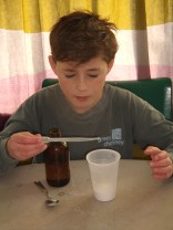 Louis carefully counts drops of oil from his pipette.