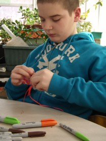 Trystian carefully sews up his project.