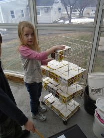"Laura stacks the cartons for them to dry. Her classmate Cameron exclaims, ""This is like Don't Break the Ice!"""