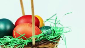 stock-footage-easter-eggs-background-colorful-easter-eggs-in-a-basket-with-green-grass-decoration-white